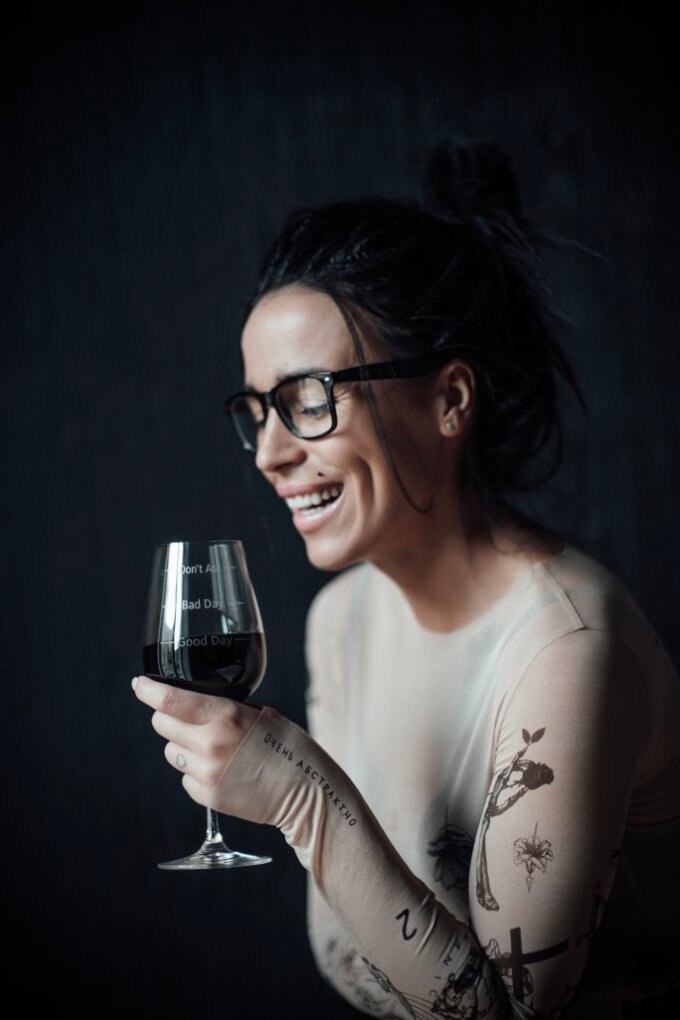 alcoholism rehab san diego female portrait pretty brunette girl millennial holds a glass of red wine and laughs smiles intoxicated