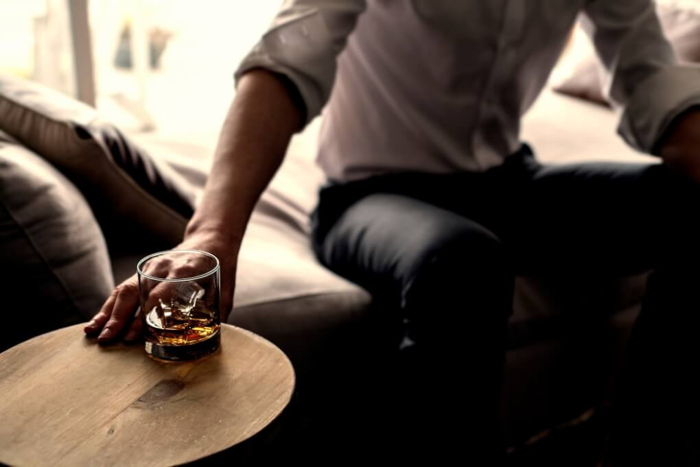 sign of mental health disorder man reaching for whiskey on ice alcoholic cocktail liquor drink while sitting on a comfy lounge chair