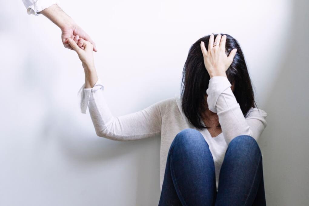 woman looking depressed hand on head social distancing illness mental illnesss disease psychology
