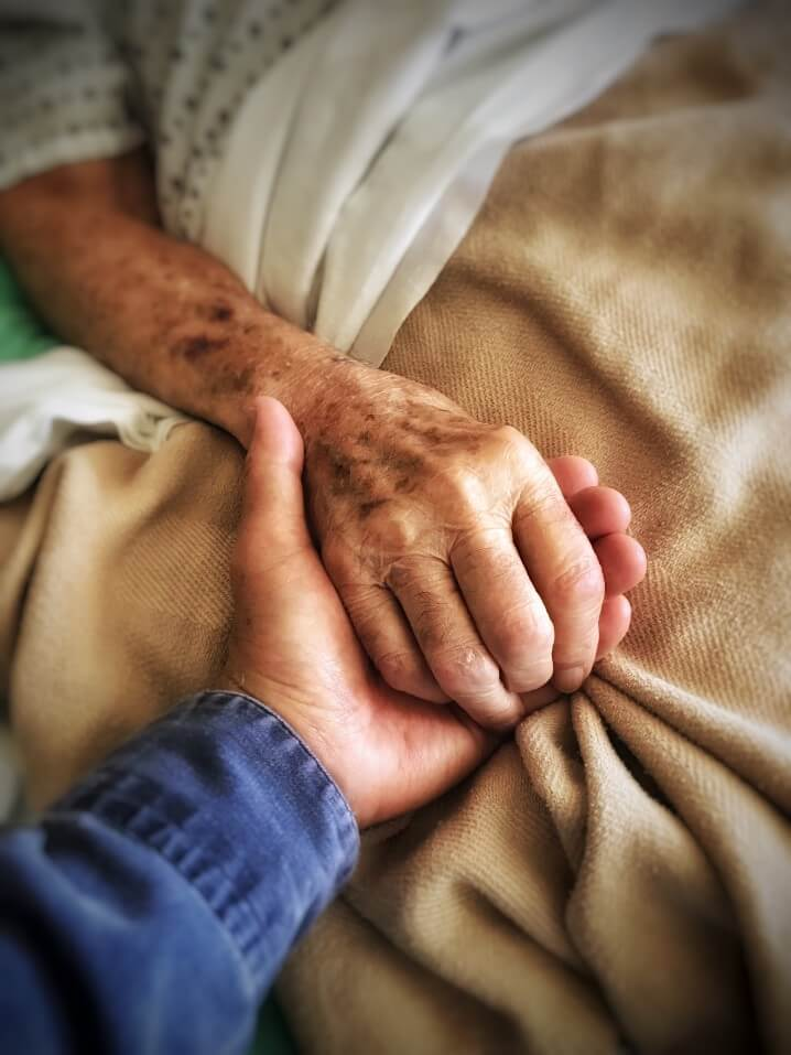 grieving grief son holds his dying father s hand at hospital bedside