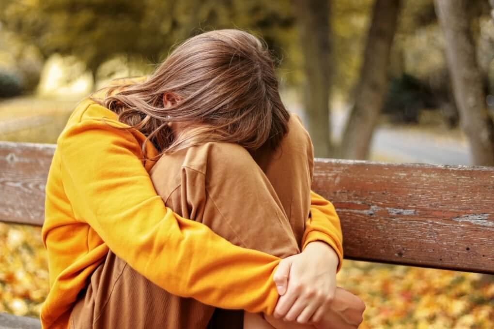 how to know you are suffering lonely upset heartbroken teenager girl crying sitting on bench outdoors hiding her face in knees